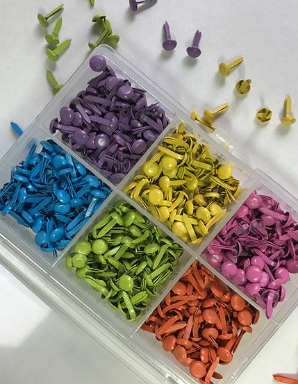 Package of 600 bright mini brads used in making articulated paper dolls